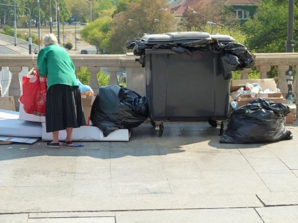 Aletrsarmut. Eine Frau sucht nach Pfandflaschen im Müll.
