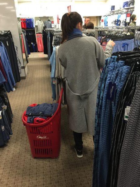 Kleidereinkauf per Rollwagen in New York. Massenweise kaufen Verbraucher Textilien ein.