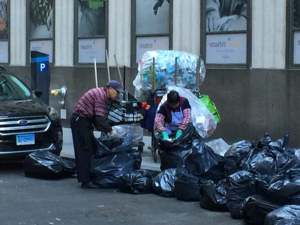 Diese beiden älteren Bürger kommen jeden Nachmittag, um in den schwarzen Müllbeuteln nach Pfandgut zu suchen. Es stinkt fürchterlich.